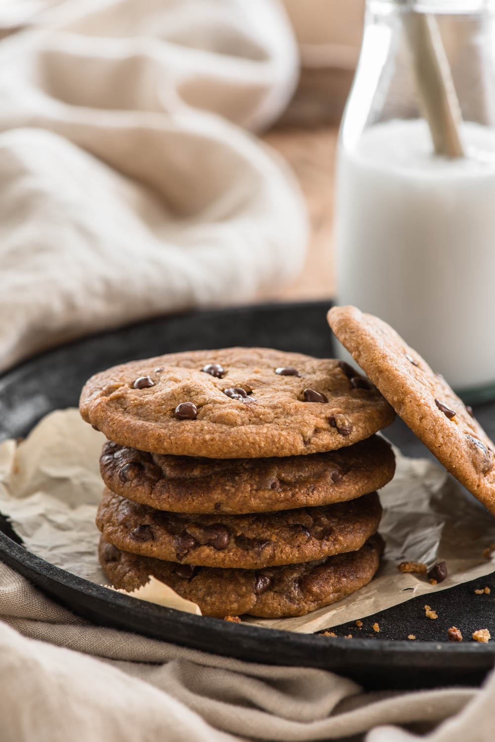 stack of chocolate chip cookies with milk glass in the background
