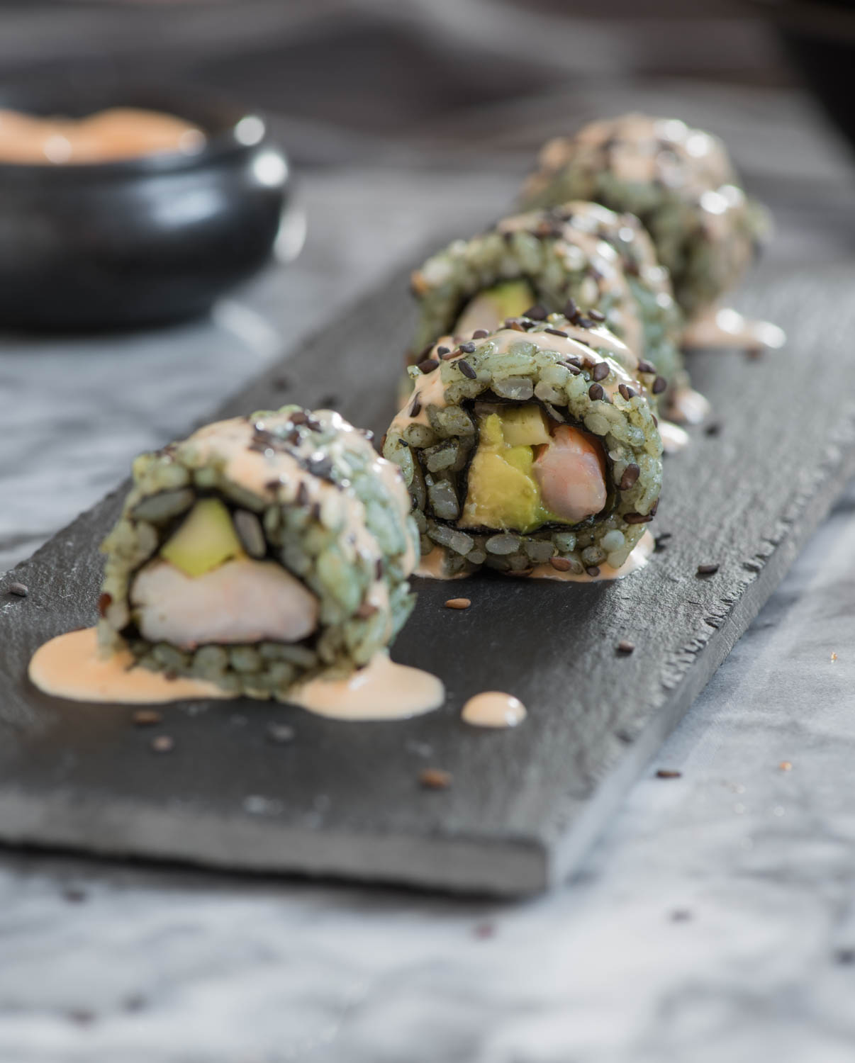 close up shot of healthy sugar free sushi rolls with shrimp and avocado - naturally colored and topped with spicy mayo sauce