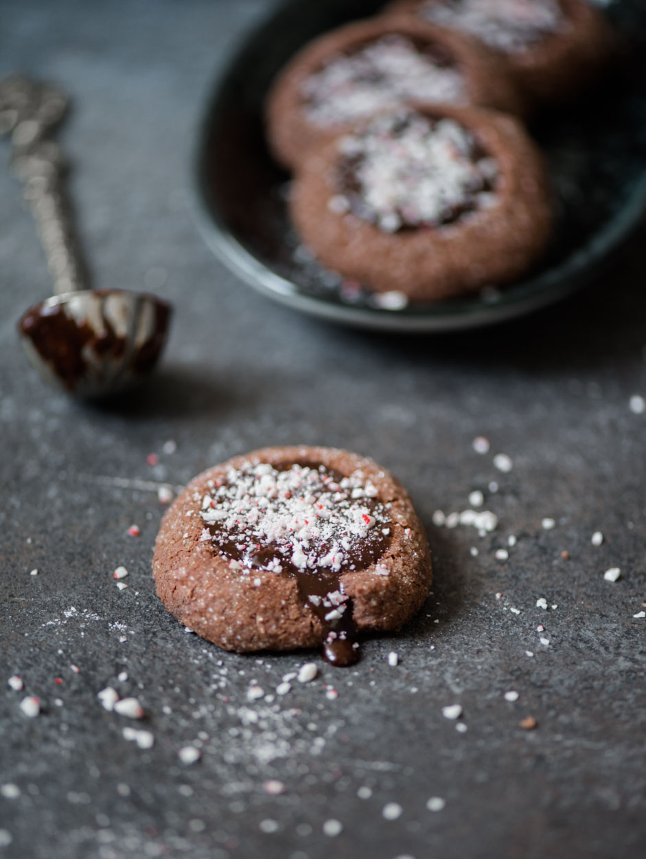 Chocolate ganache dripping from chocolate peppermint thumbprint cookie
