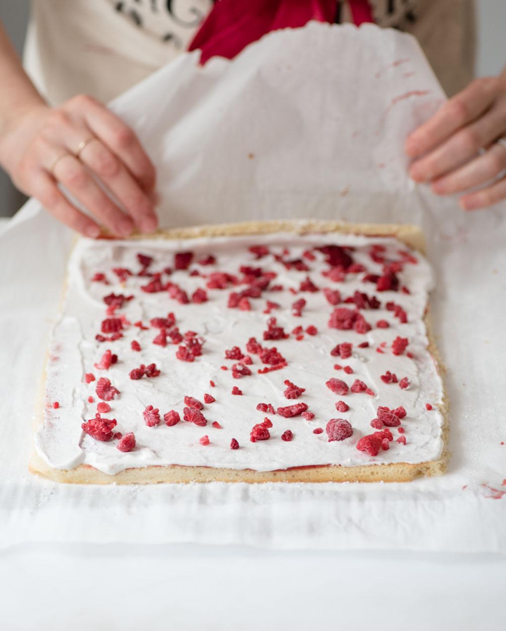 female beginning to roll raspberry lemon cake roll