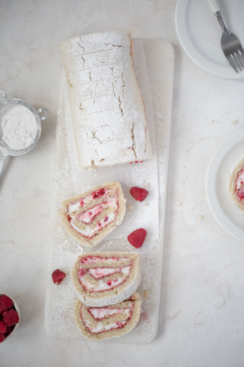 A few slices of raspberry lemon swiss rolls on a marble slab and a couple of plates.