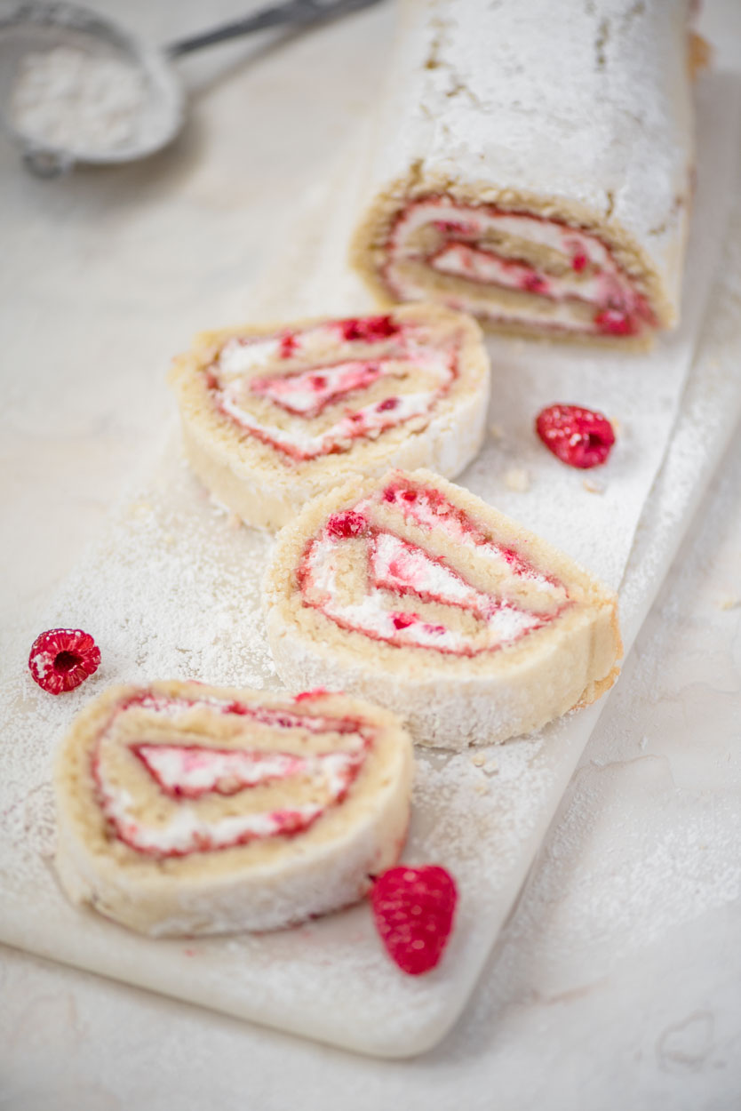 a few slices of raspberry lemon roll on a slab of marble