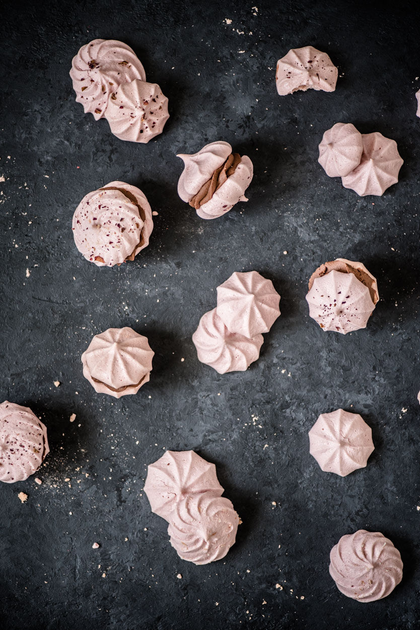 Pink pavlova cookie sandwiches filled with whipped fudge on dark surface