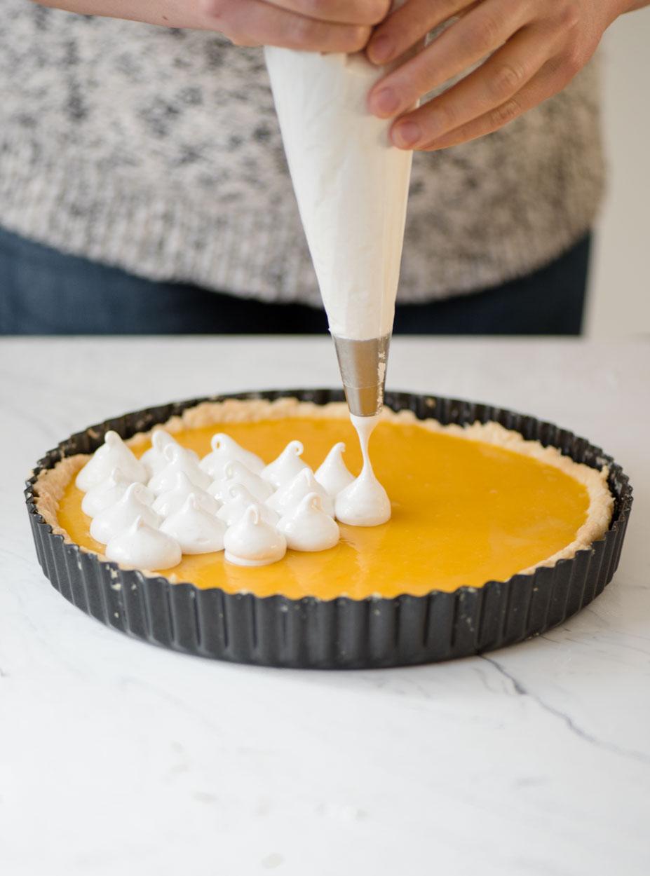 hands piping meringue on lemon pie
